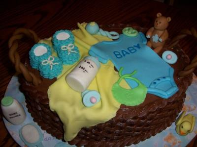 picture of a blue onesie boy bassinet cake