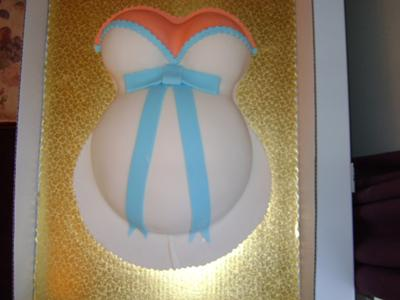 image of a white baby bump cake with blue ribbon