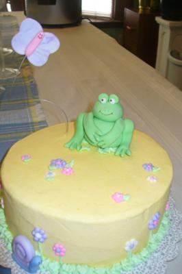 picture of a yellow cake with a frog, butterfly, and flowers
